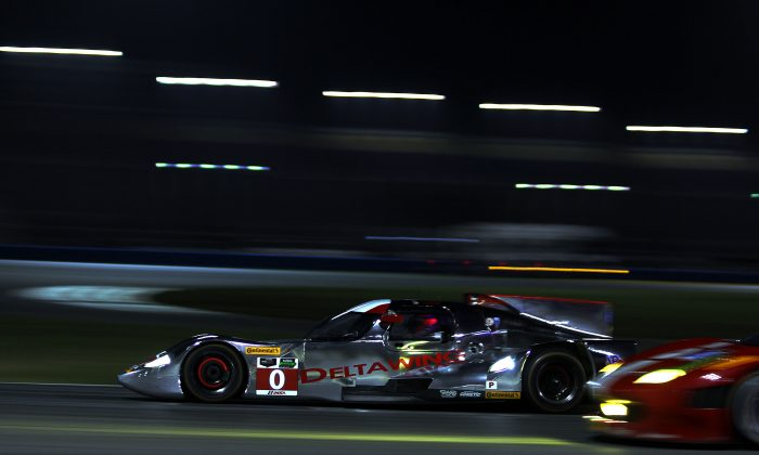 The DeltaWing DWC13 sweeps past one of the many GTD Ferraris on the sort straight connecting Daytona International Speedway's East and West Horseshoes during TUSCC Roar Before the 24 night practice, Jan. 4, 2014. (Chris Jasurek/Epoch Times)