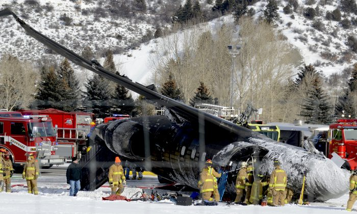 Emergency crews work near a passenger plane that crashed upon landing at the Aspen-Pitkin County Airport in Aspen, Colo., Sunday, Jan. 5, 2014. (AP Photo/The Aspen Times, Leigh Vogel)