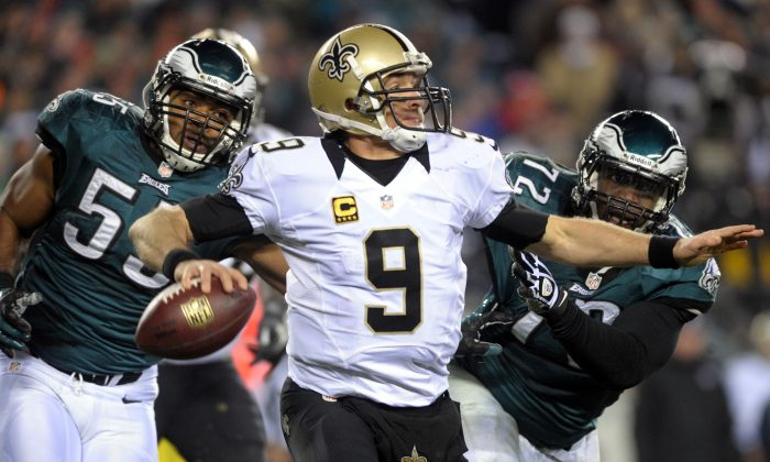 Saints quarterback Drew Brees, (9) throws the ball as he is pressured by Eagles linebacker Brandon Graham, (55) and defensive end Cedric Thornton (72) during an NFL wild-card playoff football game, Saturday, Jan. 4, 2014, in Philadelphia. (AP Photo/The Express-Times, Matt Smith)