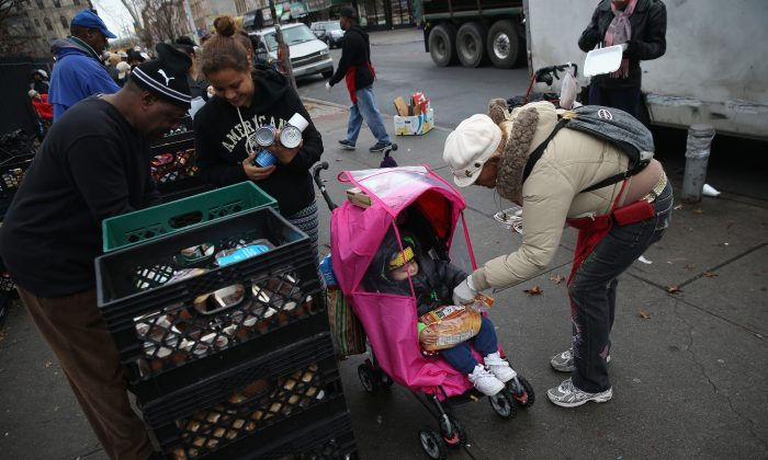 Residents receive free food as part of a Bowery Mission outreach program in Brooklyn, New York, on Dec, 5, 2013. The Christan ministry said it has seen a spike in need since food stamps to low-income families were reduced in November with cuts to the federal Supplemental Nutrition Assistance Program. (John Moore/Getty Images)