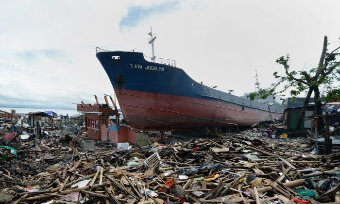A cargo ship swept ashore at the height of Super Typhoon Haiyan still rest amongst debris and destroyed houses weeks after the storm in the coastal city of Tacloban, Leyte province, on December 24, 2013.  (TED ALJIBE/AFP/Getty Images)