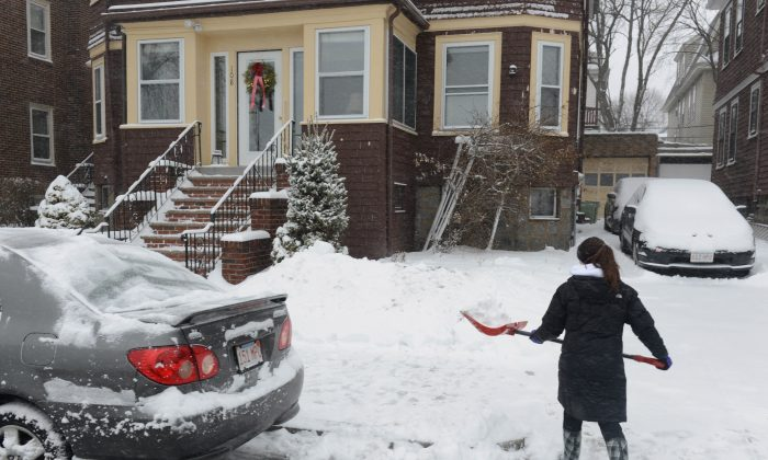 A woman shovels snow on Bayswater Street January 2, 2014 in East Boston, Massachusetts. An overnight blizzard is due to hit along the Northeast U.S. with six to twelve inches of accumlutation expected in the Boston area along with costal flooding.  (Photo by Darren McCollester/Getty Images)