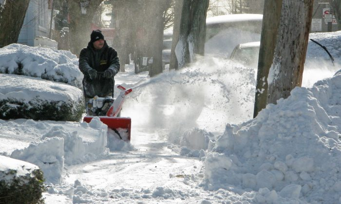 A man clears a sidewalk using a snowblower in the Bronx, New York, Jan. 3, 2014. Don Emmert/AFP/Getty Images)