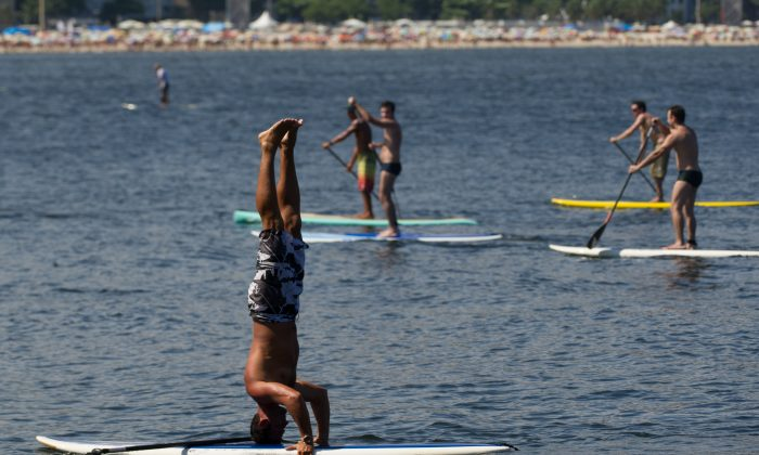 People enjoy standup paddle at Copacabana beach in Rio de Janeiro, Brazil, on January 4, 2014. (YASUYOSHI CHIBA/AFP/Getty Images)