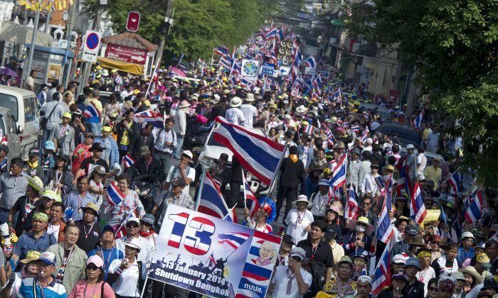 Thousands of Thai opposition protesters marched through Bangkok on Jan 5 to demand the prime minister step down, in a 'warm-up' for their planned occupation of the city.  (Pornchai Kittiwongsakul/AFP/Getty Images)