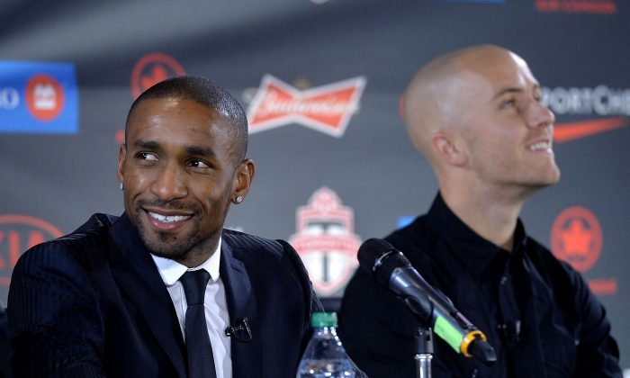 Toronto FC's two newest designated player signings Jermain Defoe (L) and Michael Bradley survey the crowd at a press conference in Toronto on Jan. 13, 2014. (Jag Gundu/Getty Images)