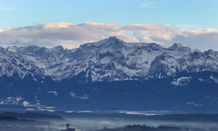 Fog rises from the valley and the church of Marktoberdorf, southern Germany, as in background can be seen an Alps panorama on January 19, 2014. (KARL-JOSEF HILDENBRAND/AFP/Getty Images)