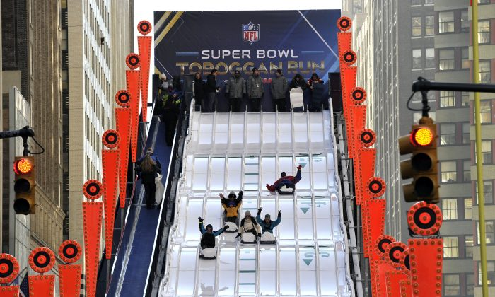Fans come down a toboggan run on NFL's Super Bowl Boulevard during in preparation for Super Bowl XLVIII with the Denver Broncos and the Seattle Seahawks, in Manhattan, New York, Jan. 29, 2014. (Timothy Clary/Getty Images)
