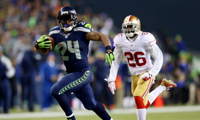 Running back Marshawn Lynch #24 of the Seattle Seahawks scores a 40-yard touchdown against cornerback Tramaine Brock #26 of the San Francisco 49ers in the third quarter during the 2014 NFC Championship at CenturyLink Field in Seattle, Washington, January 19, 2014. (Ronald Martinez/Getty Images)