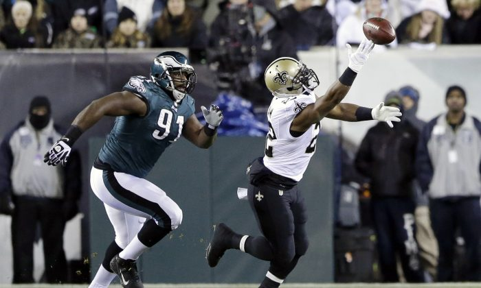 New Orleans Saints' Mark Ingram, right, cannot pull in a pass as Philadelphia Eagles' Fletcher Cox (91) pursues during the first half of an NFL wild-card playoff football game, Saturday, Jan. 4, 2014, in Philadelphia. (AP Photo/Julio Cortez)