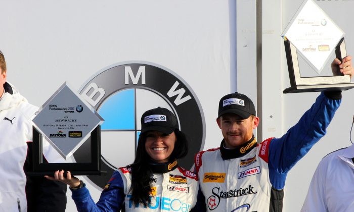Ashley Freiberg and Shelby Blackstock raise their second place trophies at the podium ceremony following the CTSCC BMW Performance 200 at Daytona Friday. The pair was later awarded the win. (Chris Jasurek/Epoch Times)