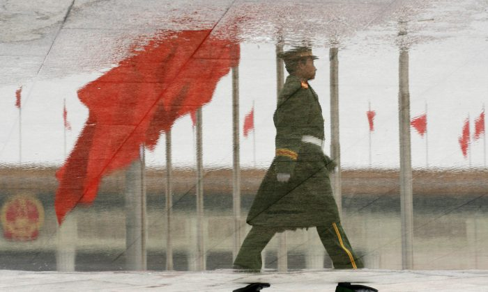 This inverted image shows a para-military policeman reflected in a pool of water as he patrols Tiananmen Square while provincial level meetings of the National Peoples Congress are held at the Great Hall of the People in Beijing, 08 March 2006. (MARK RALSTON/AFP/Getty Images)