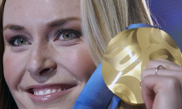 In this Feb. 17, 2010 file photo, Lindsey Vonn of the United States, shows the gold medal she won in the Women's downhill, during the medal ceremony at the Vancouver 2010 Olympics in Whistler, British Columbia, Canada. (AP Photo/Luca Bruno)