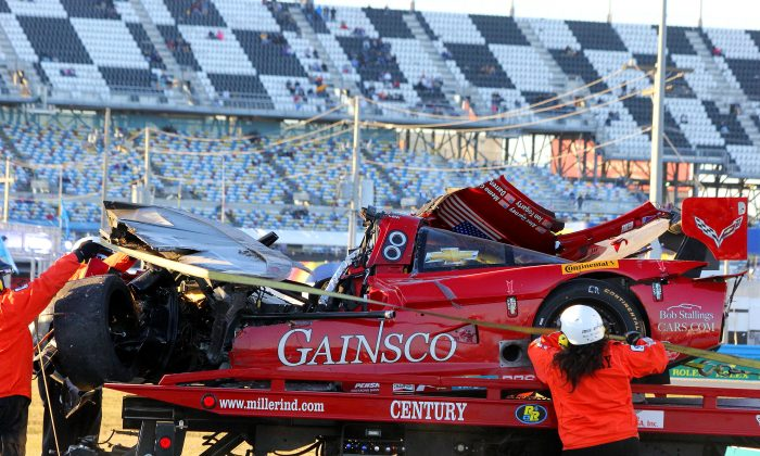 Track workers winch the ruined #99 Gainsco Riley-Corvette onto a flatbed. (Chris Jasurek/Epoch Times)