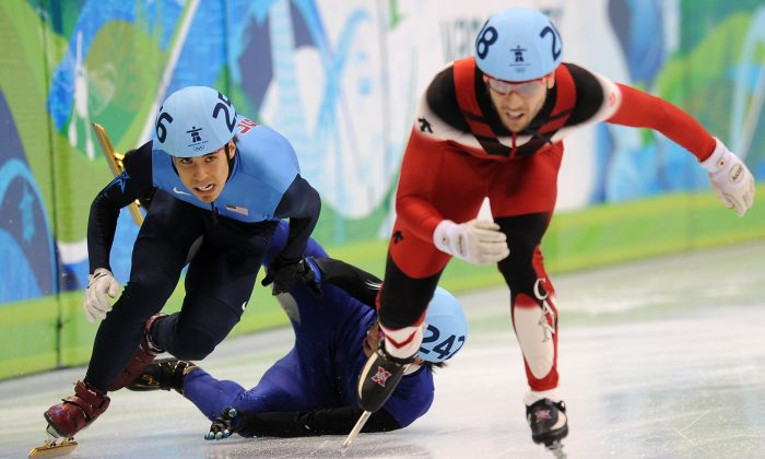 Apolo Anton Ohno, left, ompetes with Canada's Canada's Francois-Louis Tremblay as South Korea's Ho-Suk Lee (C down) falls in the Men's 500 m short-track semifinals at the Pacific Coliseum in Vancouver, during the 2010 Winter Olympics. (Robyn Beck/AFP/Getty Images)