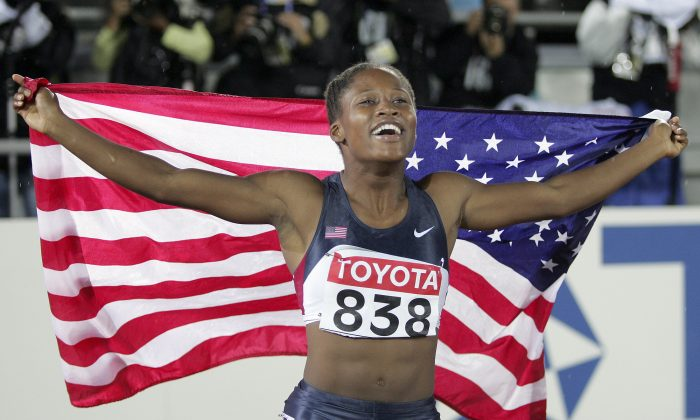 Lauryn Williams of the US celebrates with the Stars and Stripes after winning the gold medal  in the final of the Women's 100 meters  at the World Athletics Championships in Helsinki, Monday Aug. 8, 2005.(AP Photo/Martin Meissner)