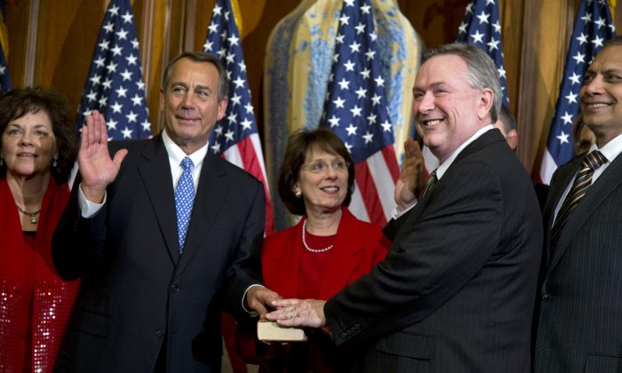 In this Jan. 3, 2013 file photo, Rep. Steve Stockman, R-Texas, second from right, participates in a mock swearing-in ceremony with Speaker of the House Rep. John Boehner, R-Ohio, for the 113th Congress in Washington. (AP Photo/ Evan Vucci, File)