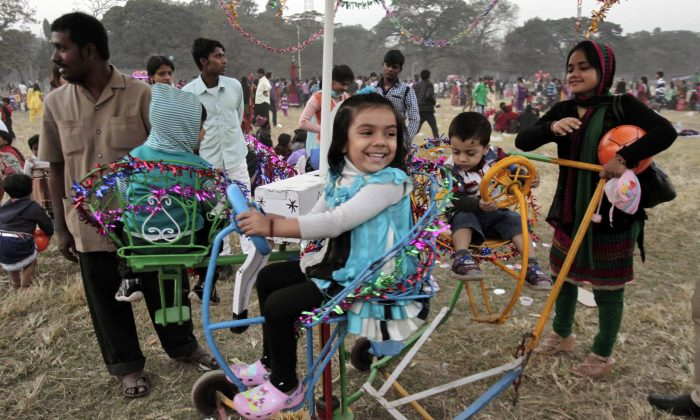 Young Indian children enjoy a ride on a mobile merry go round at a park in Kolkata, India, Wednesday, Jan. 1, 2014. Many people visited the public park on the first day of the New Year. (AP Photo/Bikas Das)