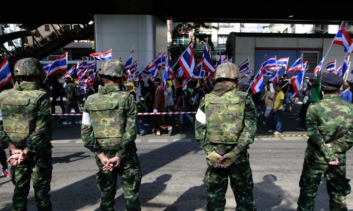 Thai soldiers watch anti-government protesters march on the street past them during a rally Wednesday, Jan. 22, 2014 in Bangkok, Thailand.  (AP Photo/Wason Wanichakorn)