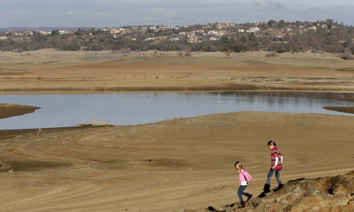 With the edge of Folsom Lake, Calif., more than 100 yards away, Gina, 8, left, and Sydney, 9, Gerety walk on rocks that are usually at the waters edge,  Thursday Jan. 9, 2014.  Gov. Jerry Brown said he would meet Thursday with his recently formed drought task force to determine if an emergency declaration is necessary as California faces a serious water shortage. Reservoirs in the state have dipped to historic lows after one of the driest calendar years on record.(AP Photo/Rich Pedroncelli)