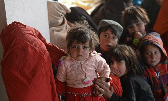 Afghan children look on as they wait to visit a doctor in a mobile clinic of the French NGO, Medical Refresher Courses for Afghans (MRCA) in the north of Kabul on Dec. 17, 2013. (Massoud Hossaini/AFP/Getty Images)