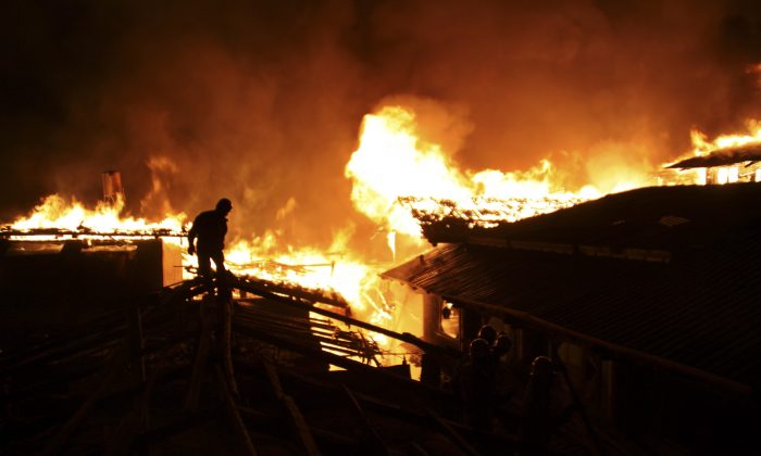 A firefighter works on a roof of a wooden building while a fire ravages ancient Dukezong town in Shangri-la county, in southwestern China's Yunnan province, Saturday Jan. 11, 2014. The 10-hour inferno has razed the ancient Tibetan town in the province that's popular with tourists. (AP Photo) CHINA OUT