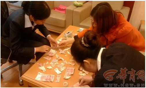 Screenshot showing employees at a branch of China Construction Bank reassembling cash torn up by a young by in Shaanxi province. (Screenshot/hsw.cn)