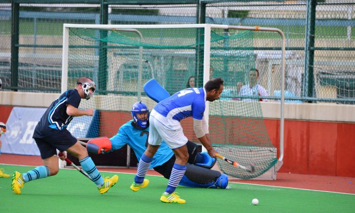 HKFC will be under pressure to retain the top position of the HKHA Premier Division standings ... Goalie for HKFC, Vincent Cheung, made an important save from a strike by the third-placed Punjab's Mudassar Ali Khan in their 5-all closing match before the New Year break. Cheung may need to improve on his performance in HKFC's derby match against an improving fourth-placed Valley team this coming Sunday Jan 12, 2014. HKFC will then face second-placed Khalsa the following weekend to determine who will take bragging rights at the half-way mark of the season, when the competition will split into two groups. (Bill Cox/Epoch Times)