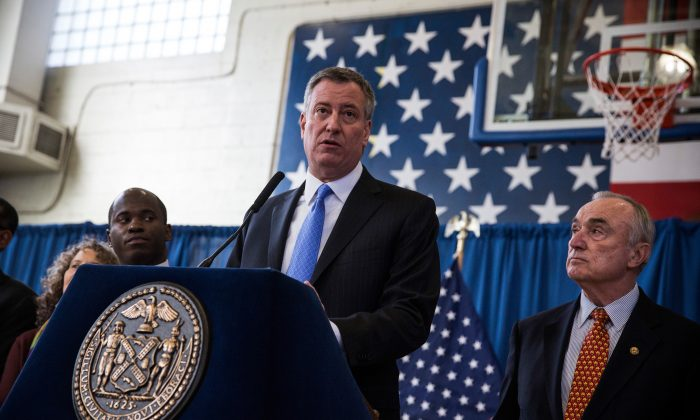 Mayor Bill de Blasio (C) and Police Commissioner Bill Bratton (R) at a press conference as, at a recreation center in Brownsville, Brooklyn, New York, Jan. 30, 2014. (Andrew Burton/Getty Images)