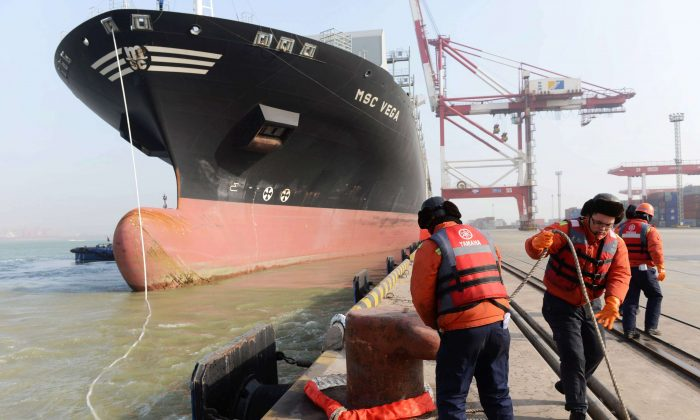 Workers prepare for a container ship to berth at the port of Qingdao, in northeast China's Liaoning province on January 20, 2014.