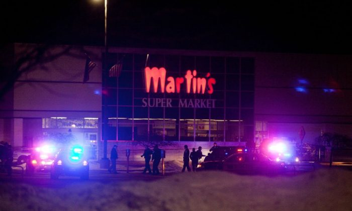 Emergency personnel respond to a shooting inside Martin's Supermarket in Elkhart, Ind., late Wednesday, Jan. 15, 2014.   A man fatally shot two women inside the grocery store and was lining up to shoot a third person when police officers tracked him down and killed him, authorities said. Elkhart police received a call about a gunman at Martin's Super Market about 10 p.m. Wednesday, Indiana State Police Sgt. Trent Smith said Thursday. The 22-year-old gunman used a semi-automatic handgun to shoot and kill a 20-year-old employee and a 44-year-old shopper, Smith said. The victims' bodies were found about 12 aisles apart. (AP Photo/The Elkhart Truth, Jon Garcia)
