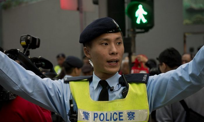 A Hong Kong policeman urges people to disperse after a minor scuffle between protesters during a pro-democracy demonstration in Hong Kong on Jan. 1, 2014. Thousands marched in Hong Kong to demand a greater say in how their future leaders will be chosen, expressing fears that China will limit long-awaited political reforms. (Alex Ogle/AFP/Getty Images)