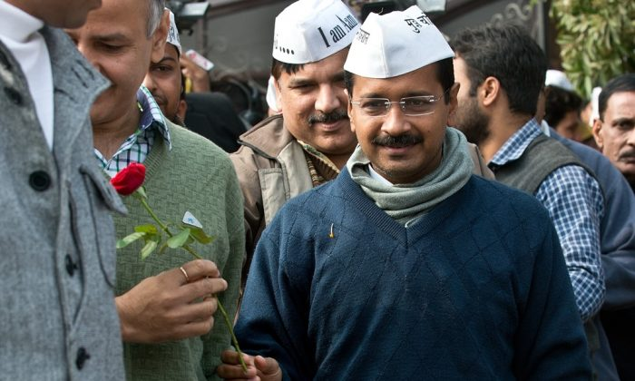 Aam Admi Party (AAP) leader Arvind Kejriwal (R) receives a rose as he arrives to address a press conference at the party headquarters in Ghaziabad, on the outskirts of New Delhi, on December 23, 2013. . The youngest Indian political party won the vote of trust in the Delhi Assembly on January 2.  The 28-member party now has the support of eight Congress members, and crossed the half way barrier of the 70-member assembly. The Bharatiya Janata Party (BJP), with its 31 members now sits in the opposition. (Prakash Singh/AFP/Getty Images)
