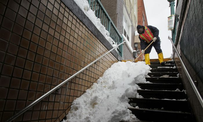 An MTA worker clears subway stairs of snow, Brooklyn borough, New York City (file photo). (Spencer Platt/Getty Images)