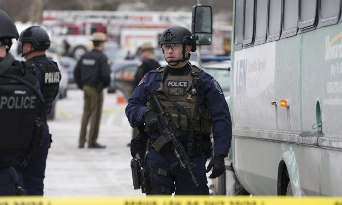 A heavily armed police officer walks on scene after a shooting at The Mall in Columbia on Saturday, Jan. 25, 2014 in Columbia, Md. Police say three people died in a shooting at the mall in suburban Baltimore, including the presumed gunman. (AP Photo/ Evan Vucci)