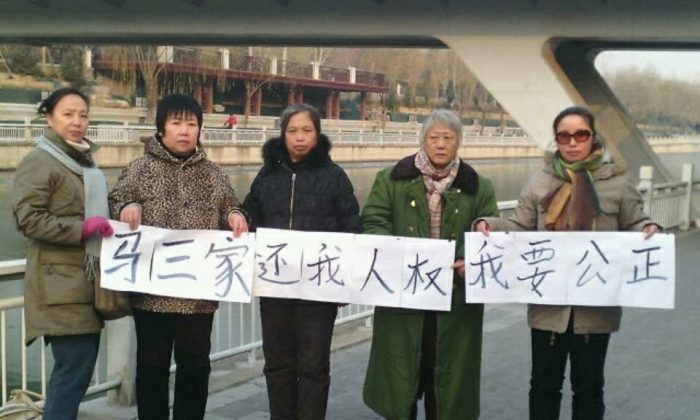 """A group of victims of the Masanjia Women's Forced Camp traveled to Beijing on Dec. 16 and held a banner saying: """"Masananjia, Return my Human Rights, I Want Justice."""" According to Human Rights Campaign in China, Hao Wei is among those pictured. (Human Rights Campaign in China)"""