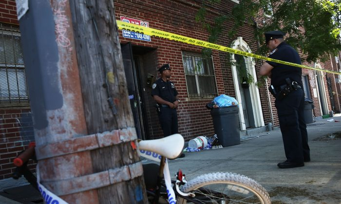 NYPD officers stand near the scene of a murder in Brooklyn, New York, June 4, 2013. (Spencer Platt/Getty Images)