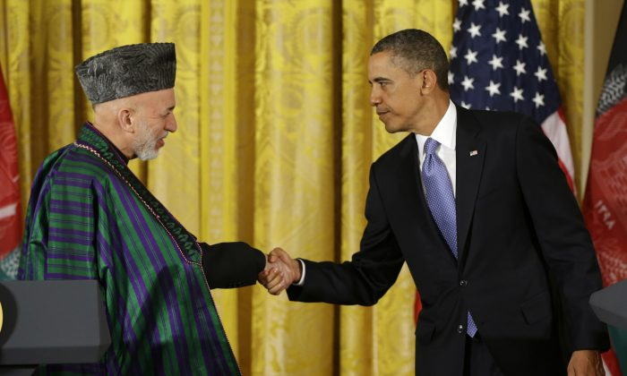 In this Jan. 11, 2013, file photo, President Barack Obama shakes hands with Afghan President Hamid Karzai at the end of their news conference in the East Room of the White House in Washington. Five years after pledging to remake the U.S. relationship with the broader Middle East and improve America's image in the Muslim world, the Obama administration's regional strategy appears to have come unhinged. (AP Photo/Pablo Martinez Monsivais, File)