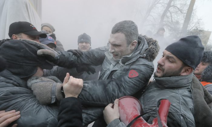 Opposition leader and former heavyweight boxing champion Vitali Klitschko (C) is attacked and sprayed with a fire extinguisher as he tries to stop clashes between police and protesters in central Kyiv, Ukraine, Jan. 19, 2014. (Efrem Lukatsky/AP)