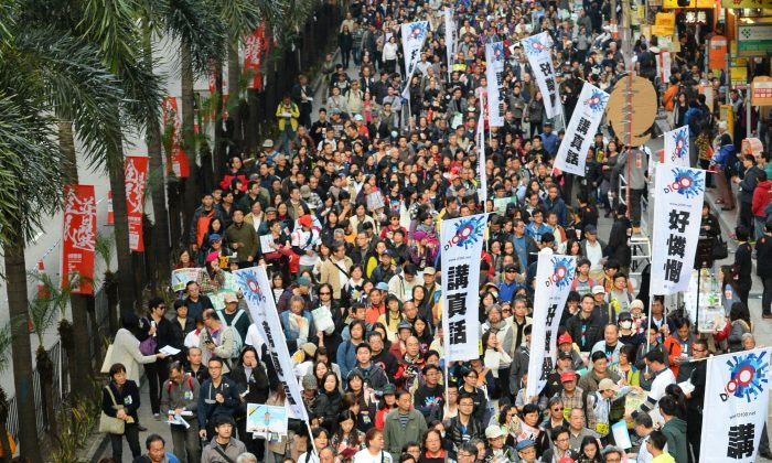 """On Jan. 1, 2014, 30,000 people took to the streets of Hong Kong to demand """"universal suffrage"""", """"CY step down"""", and """"Refuse interference from CCP"""", and so on. (Song Bilong/Epoch Times)"""