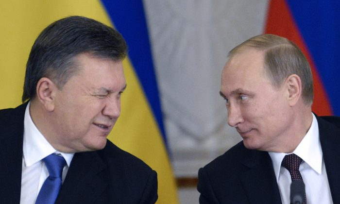 Ukrainian President Viktor Yanukovych winks at Russia's President Vladimir Putin (R) during a signing ceremony at the Kremlin in Moscow, Dec. 17, 2013. Putin said that the state energy companies of Russia and Ukraine had signed an amended agreement slashing the price Moscow charges its cash-strapped neighbor for natural gas. (Alexander Nemenov/AFP/Getty Images)