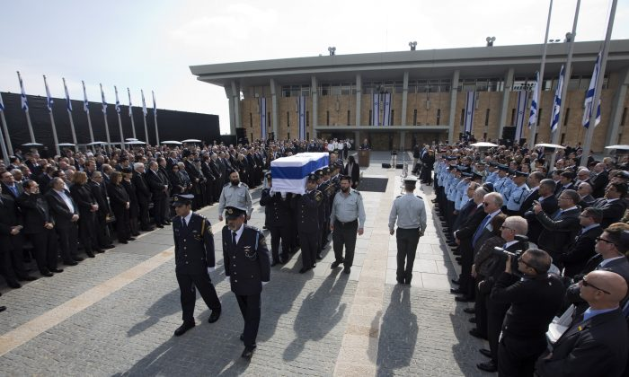 The coffin of late Israeli Prime Minister Ariel Sharon is carried after a memorial ceremony outside the Knesset, in Jerusalem, Jan. 13, 2014. (AP Photo/Sebastian Scheiner)