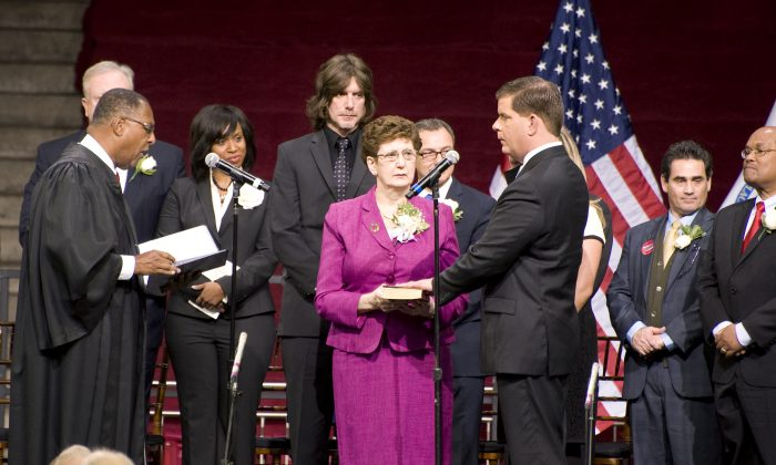 Martin J. Walsh takes the oath of office administered by Mass. Supreme Court Chief Justice Roderick L. Ireland at the Boston College Conte Forum in Boston, Mass., on Jan. 6. Walsh's left hand is on a Bible held by his mother, Mary Walsh. (Te Chen/Epoch Times)