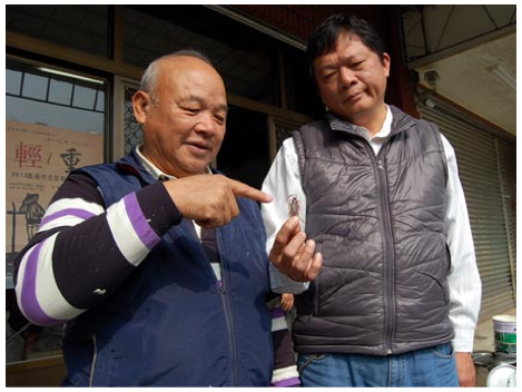 A member of the reconciliation committee points to the dead cockroach said to have caused a dispute between neighbors in Taiwan that led to a lawsuit. (Screenshot/China Times via Want China Times)