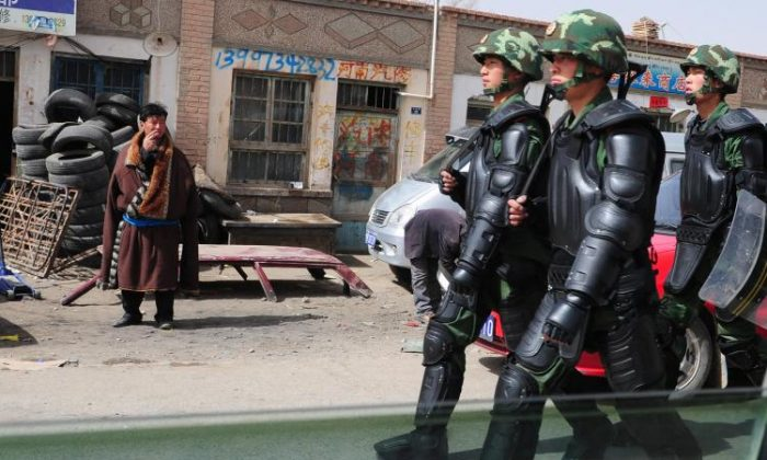 Chinese language signs are visible in this photo of a Tibetan man (L) in traditional clothing, watching as Chinese paramilitary troops in riot gear march along the streets of Guomaying, on the Tibetan plateau. Chinese policy appears aimed at replacing ethnic languages with Mandarin. (Frederic J. Brown/AFP/Getty Images)