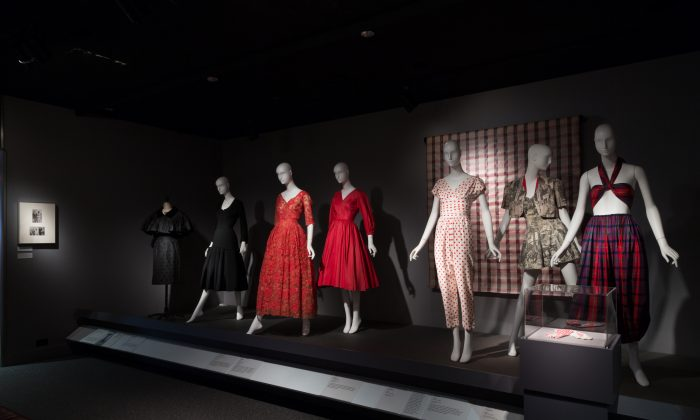 (From left) Jacques Fath (manufactured by Joseph Halpert), evening set, black taffeta and velvet, circa 1953, USA; Jacques Fath, two-piece dress, black wool twill, circa 1947, France; Christian Dior, evening dress, red lace and tulle, circa 1950, France; Anne Fogarty, dress, red silk, circa 1954, USA; Brigance, jumpsuit, red and white cotton, circa 1955, USA; bathing suit set, black and white photo-printed cotton, circa 1940, USA; Claire McCardell, ensemble, purple, red, and green cotton, 1946-1947, USA; Claire McCardell, gloves, red and white cotton and synthetic blend, circa 1953, USA; (behind) textile, automotive fabric, red plaid synthetic blend, 1958-1959, USA. (Courtesy of The Museum at FIT)