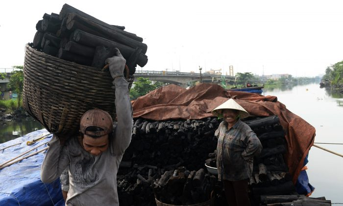 Unloading wood coal from a boat on a canal in Ho Chi Minh City, Vietnam, Nov. 20, 2013. (Hoang Dinh Nam/AFP/Getty Images)
