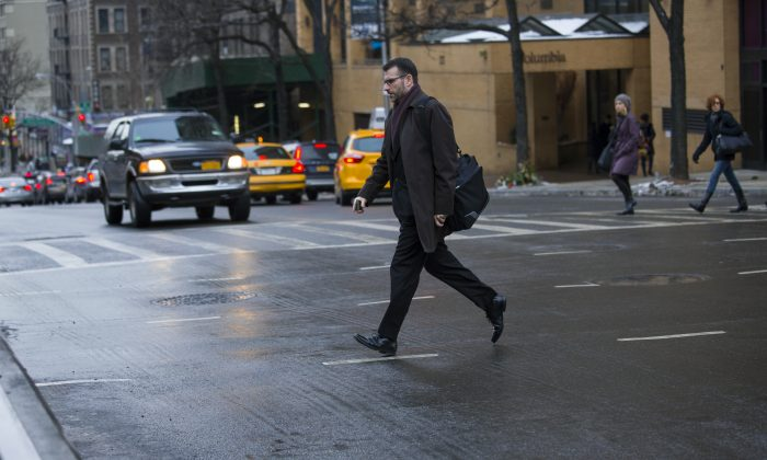 A Pedestrian moves quickly outside of a crosswalk at the busy intersection of W. 96th Street and Broadway in the Upper West Side of New York Monday, Jan. 27, 2014. Although it appears clear sometimes at this intersection, cars using turning lanes can quickly encroach on non-crosswalk areas. (AP Photo/Craig Ruttle)