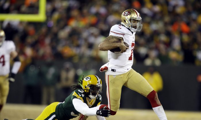 In this Jan. 5, 2014, file photo, San Francisco 49ers quarterback Colin Kaepernick (7) runs against Green Bay Packers cornerback Davon House (31) during the first half of an NFL wild-card playoff football game in Green Bay, Wis. If Kaepernick's 98-yard day in the wild-card round is any indication, it might just be that speedy QBs held under wraps during the regular season will get to strut their stuff more in the postseason. (AP Photo/Jeffrey Phelps, File)
