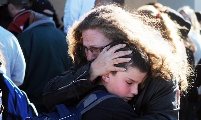 A woman hugs a student at a staging ground set up at the Roswell Mall following a shooting at Berrendo Middle School, Tuesday, Jan. 14, 2014, in Roswell, N.M. A shooter opened fire at the middle school, injuring two students before being taken into custody. (AP Photo/Roswell Daily Record, Mark Wilson)